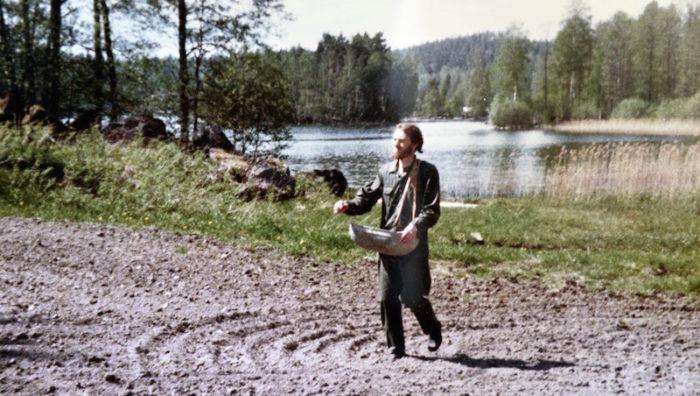 Ann-Mari har tagit bilden av Lennart när han går vid åkern nere vid sjön med en såningskorg i famnen.