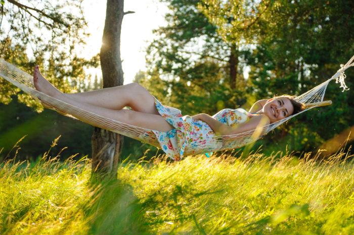 Kvinna ligger i hammock i solnedgången med vildvuxet gräs under sig.