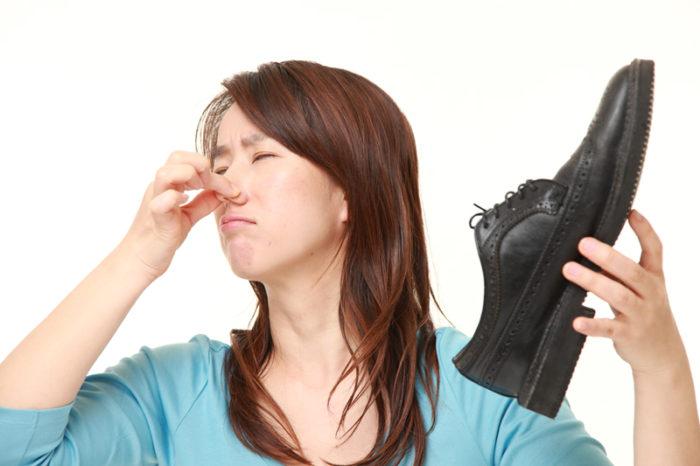 Kvinnor håller för näsan på grund av en illaluktande sko.
