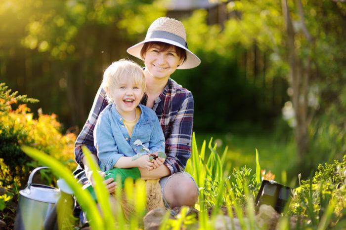 Kvinna och barn i trädgård.