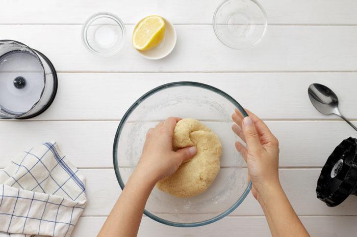 Pajdeg bakas i glasskål på vitt träbord.