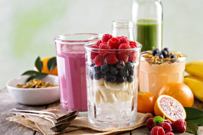 Ingredienser för smoothie i ett glas – banan, blåbär och hallon.