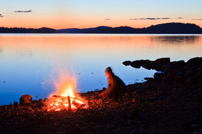 En personen sitter vid brasa vid sjö i solnedgång.