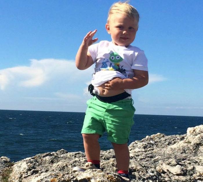 Theo Stenlundh står på en klippa och ha en sensor och insulinpump på magen. Diabetes typ 1, barn.