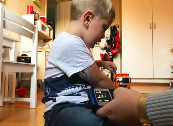 Theo Stenlundh leker och mamma Emelie Stenludh tittar på hans blodsockervärde. Diabetes typ 1 barn