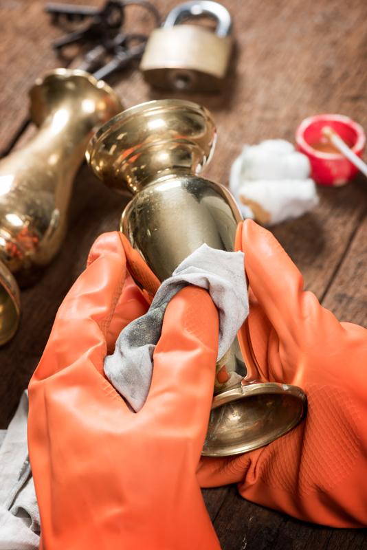 Person med orangea handskar putsar gammalt kopparföremål. 4348163380b7e