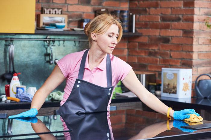 Kvinna städar i köket och rengör bänkskivan bredvid spisen.