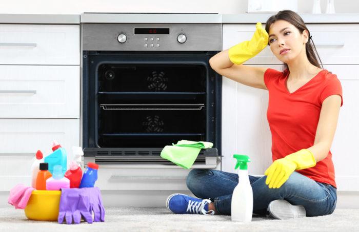 Kvinna sitter i skräddarställning framför ugn efter att ha rengjort den. På bilden finns även rengöringsmedel.